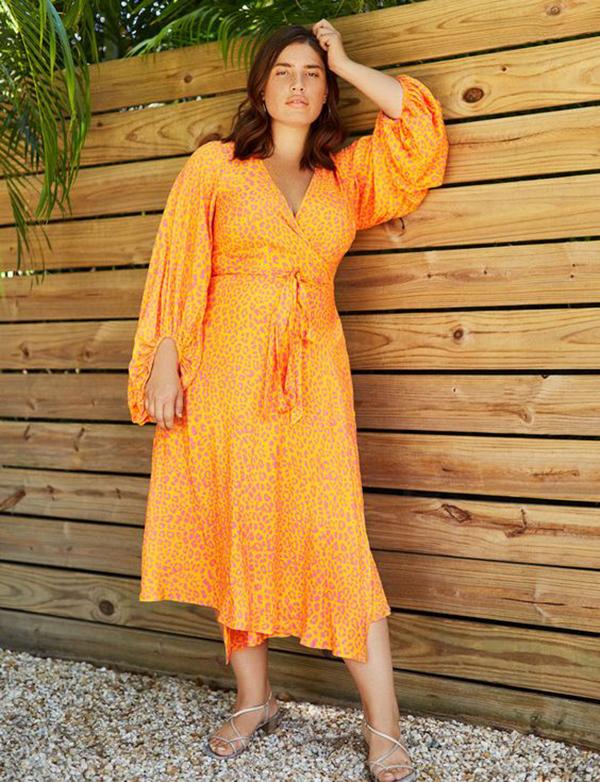 A plus-size model wearing an orange animal print dress.