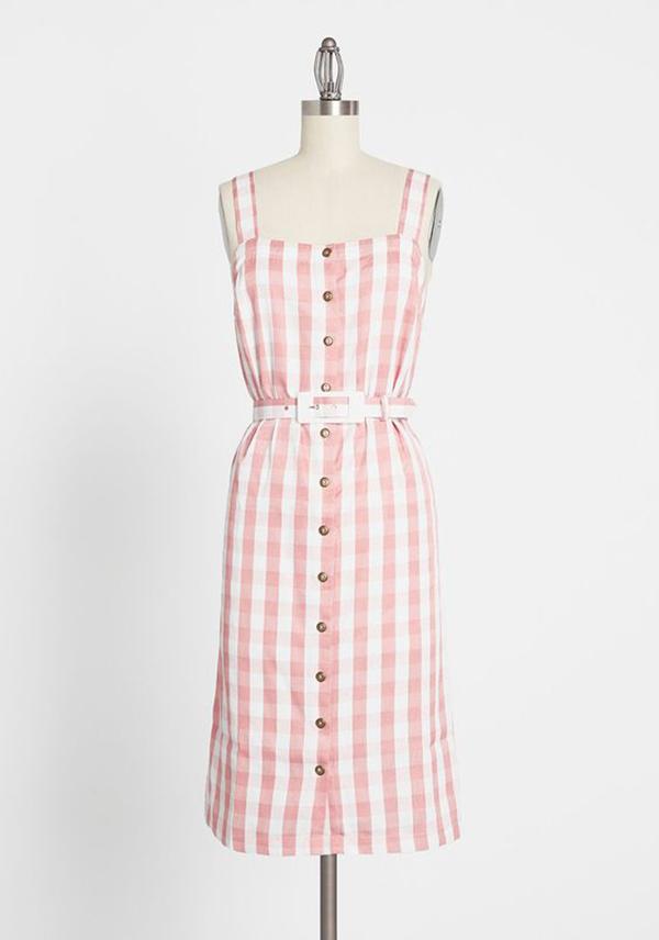 A plus-size light pink gingham midi dress.