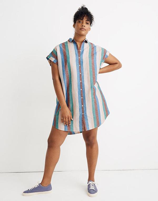 A plus-size model wearing a striped shirtdress.