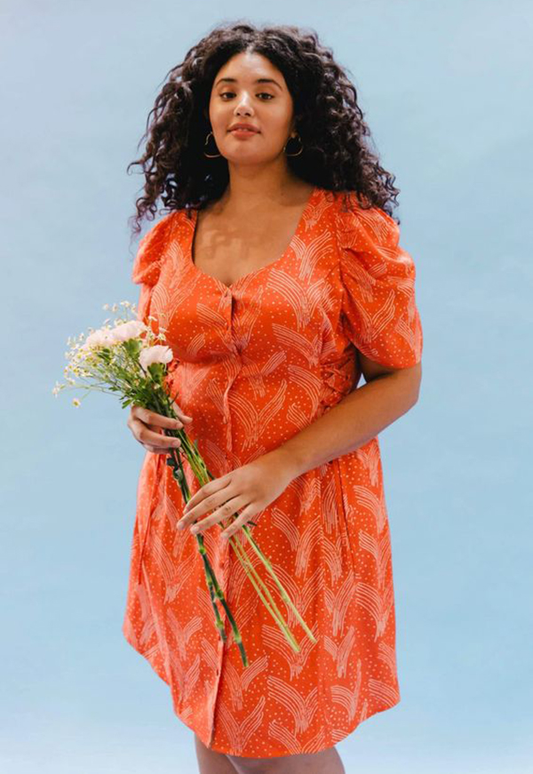 A plus-size model wearing an orange mini dress.