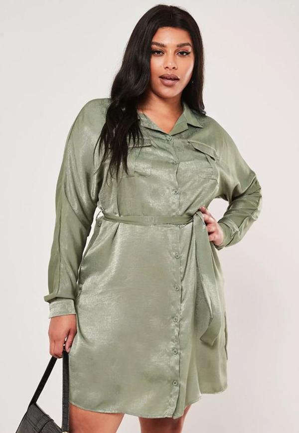 A plus-size model wearing an aqua shirtdress.