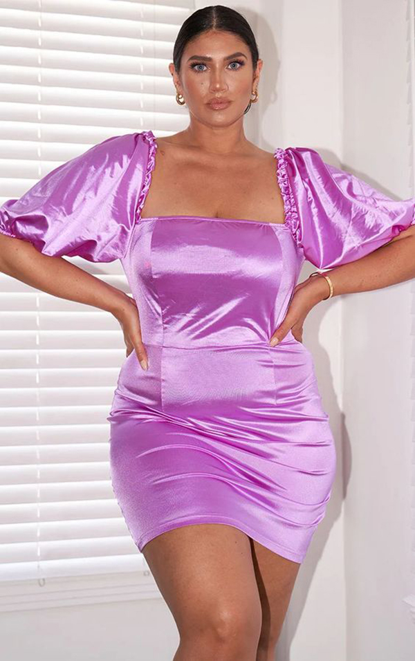 A plus-size model wearing a purple satin mini dress.