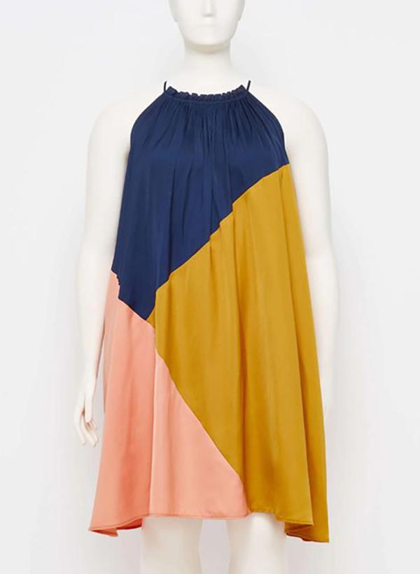 A plus-size model wearing a colorblock shift dress.
