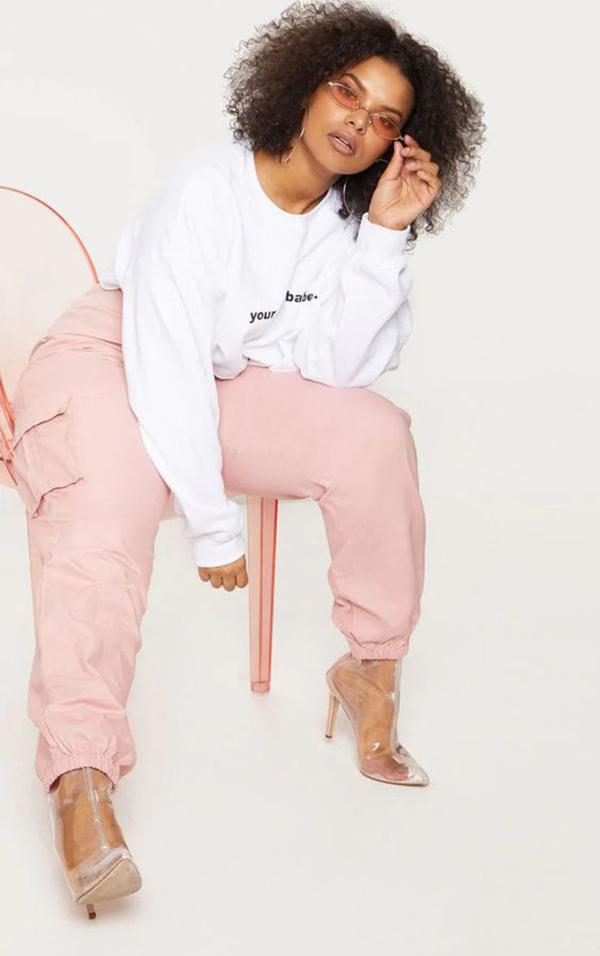 A plus-size model wearing light pink cargo pants.