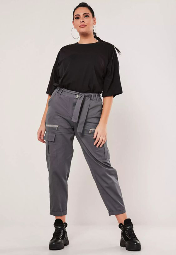 A plus-size model wearing charcoal gray cargo pants.