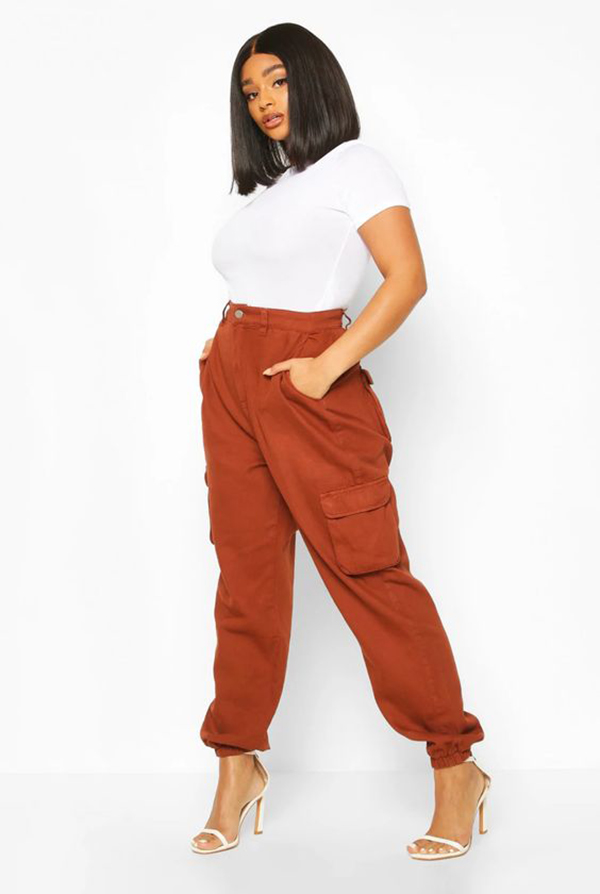 A plus-size model wearing rust cargo pants.