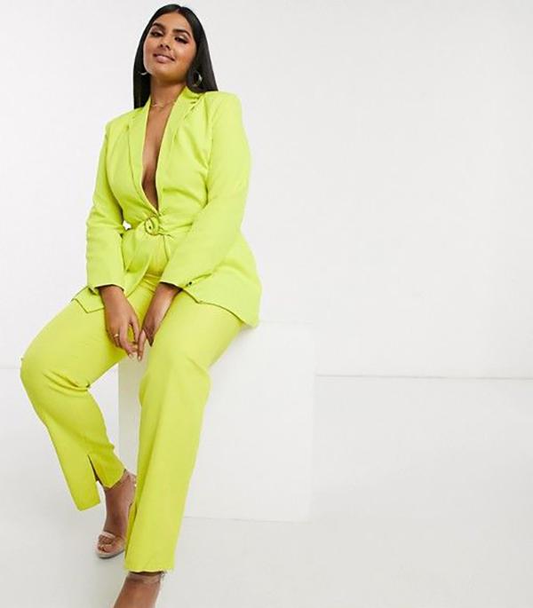 A plus-size model wearing a neon yellow-green pantsuit.