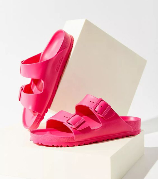 A pair of neon pink slip-on sandals.