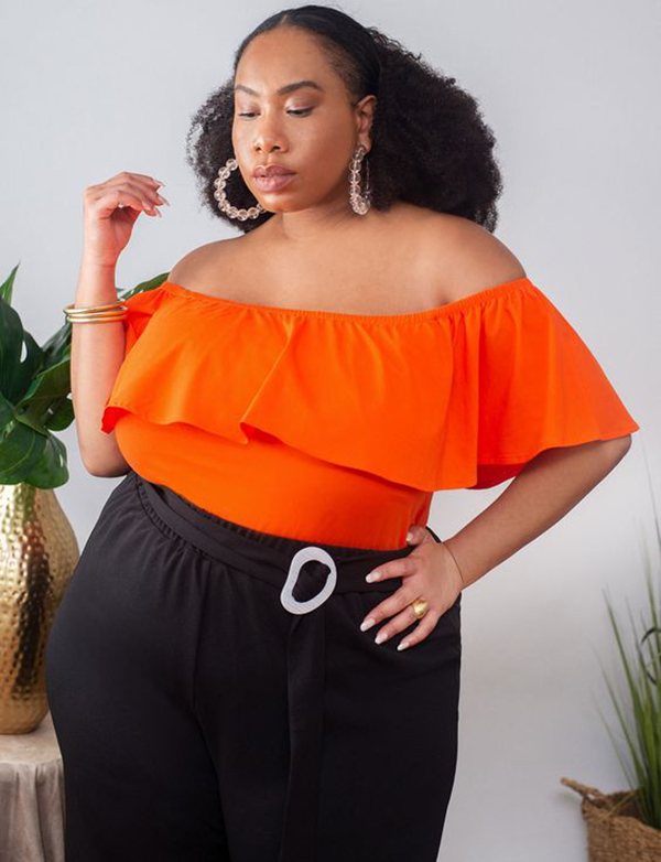 A plus-size model wearing a neon orange off-the-shoulder top.