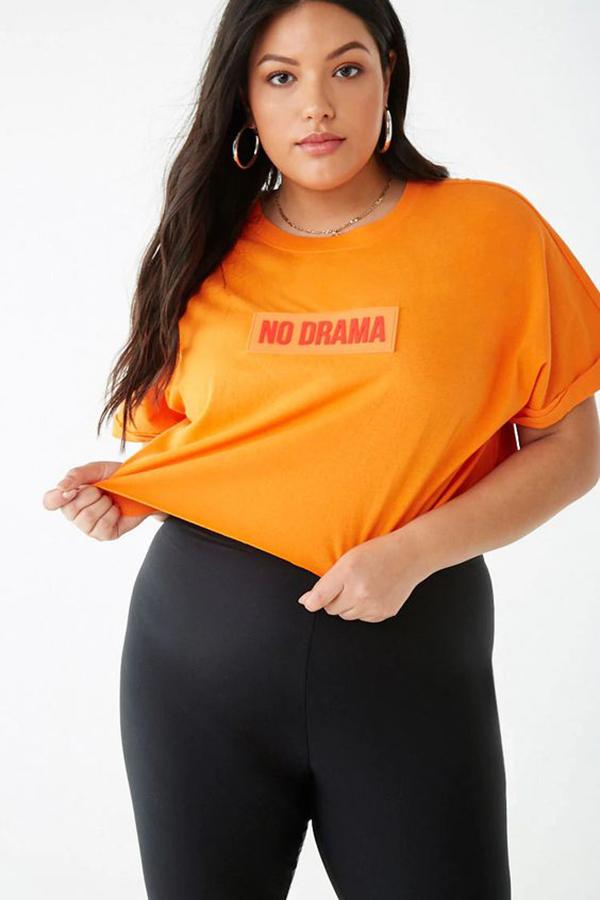 A plus-size model wearing a neon orange tee.