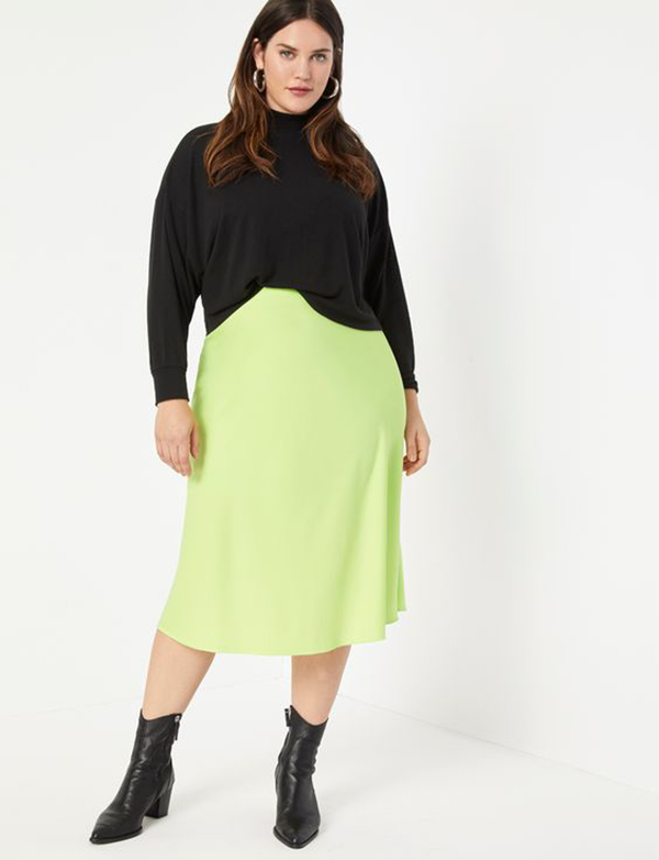 A plus-size model wearing a neon yellow-green slip skirt.