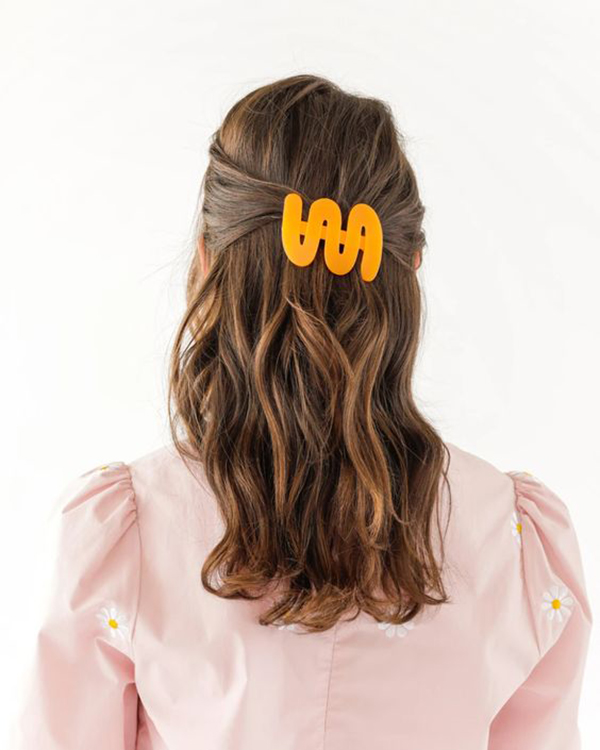 The back of a woman's hair with a neon orange barrette in it.