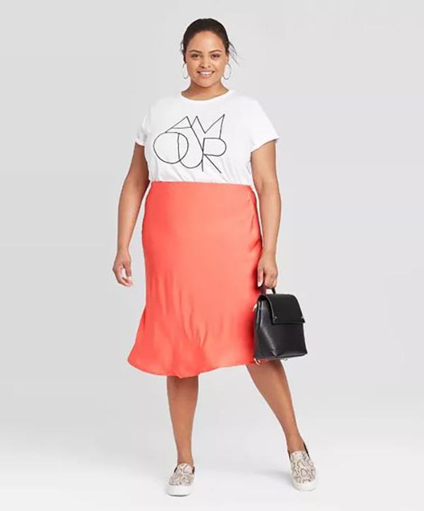 A plus-size model wearing a neon orange slip skirt.