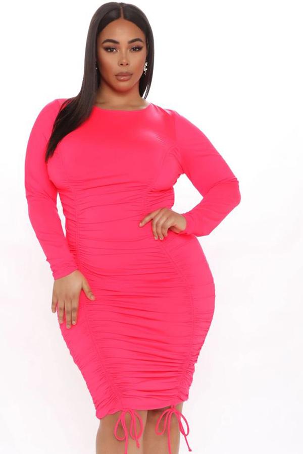 A plus-size model wearing a neon pink dress.