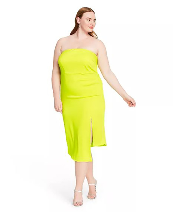 A plus-size model wearing a neon yellow-green dress.