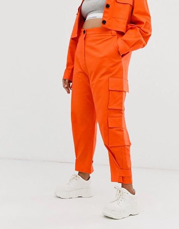 A plus-size model wearing neon orange cargo pants.