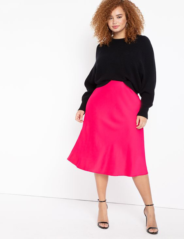 A plus-size model wearing a neon pink slip skirt.
