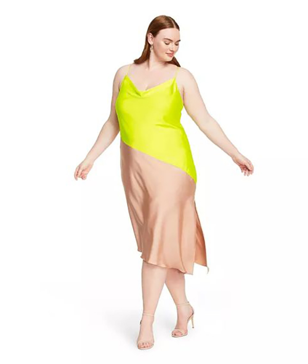 A plus-size model wearing a neon yellow-green and nude slip dress.