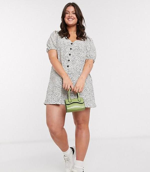 A plus-size model wearing a polka dot romper.