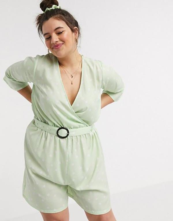 A plus-size model wearing a mint romper.