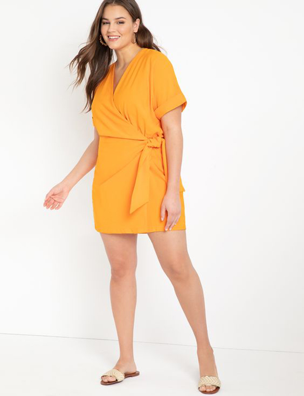 A plus-size model wearing a light orange romper.