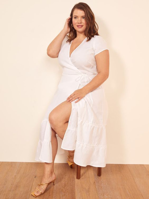 A plus-size model wearing a white wrap midi dress.