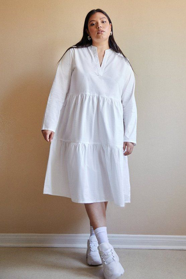 A plus-size model wearing a white midi dress.