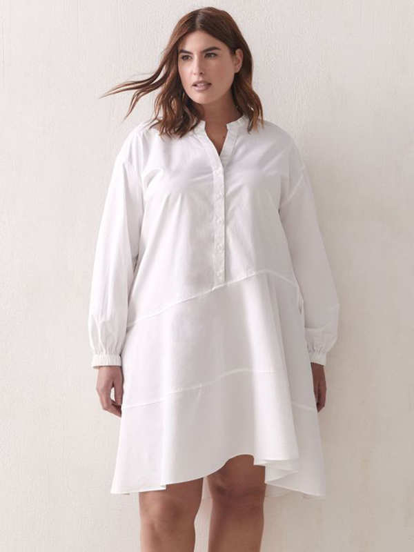 A plus-size model wearing a white shirtdress.