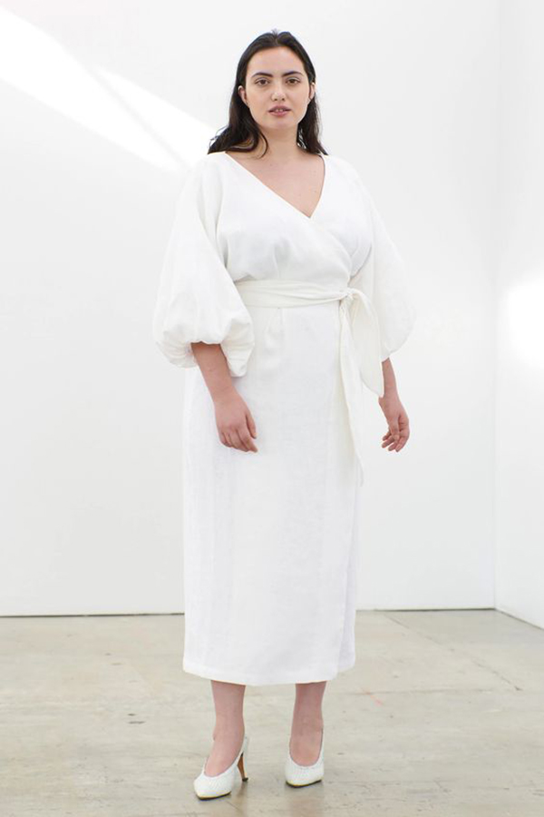 A plus-size model wearing a structured white midaxi dress.