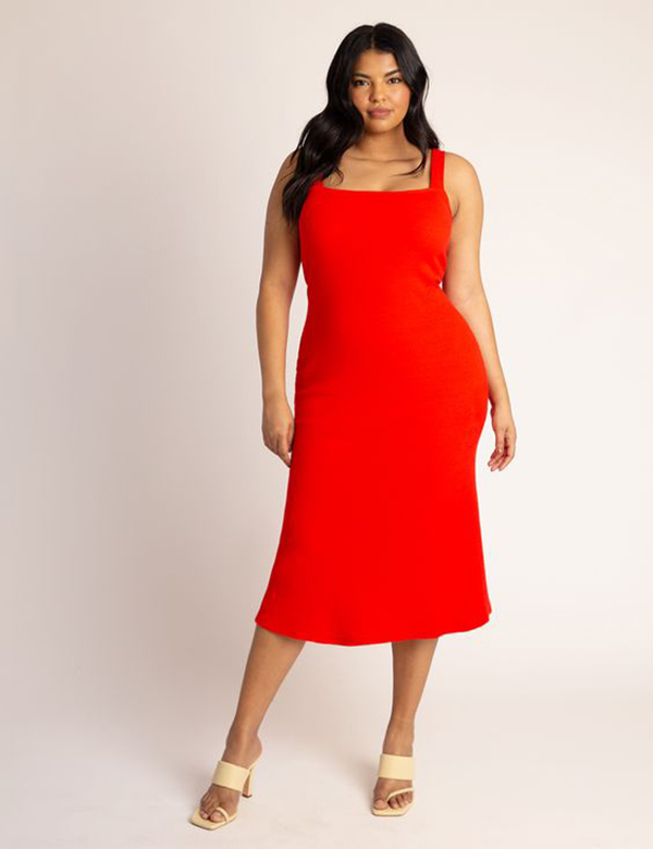 A plus-size model wearing a red dress.