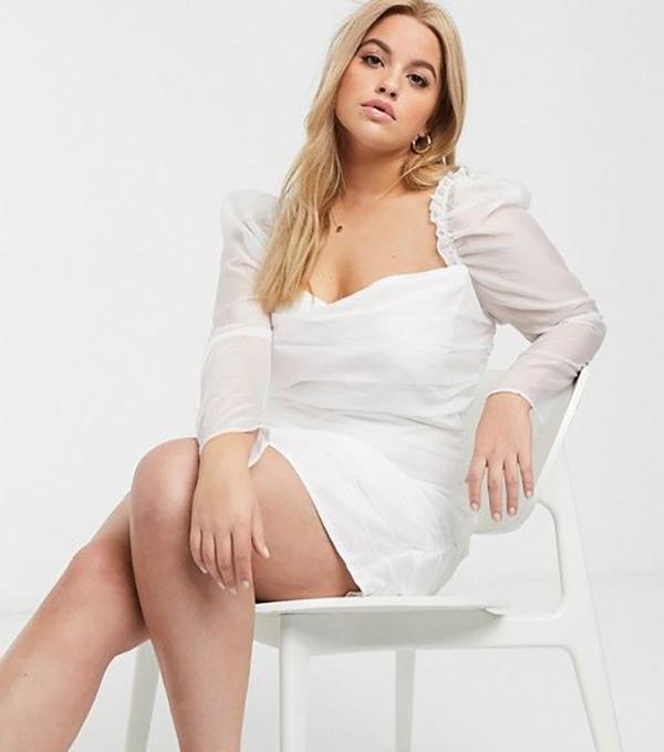A plus-size model wearing a white mini dress.