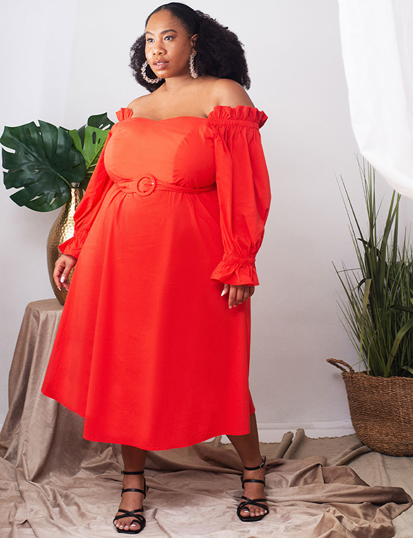 A plus-size model wearing a red off-the-shoulder dress.