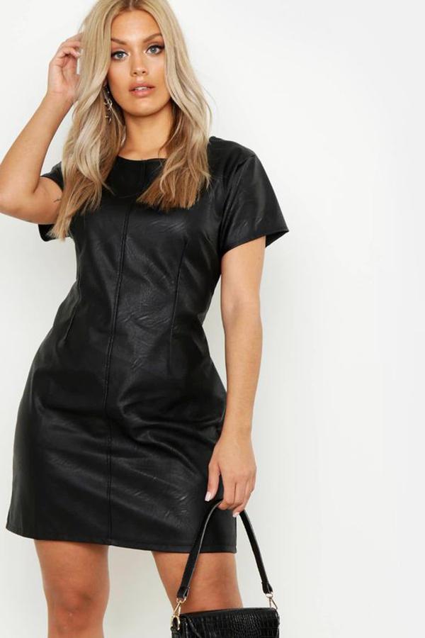 A plus-size model wearing a black leather dress.