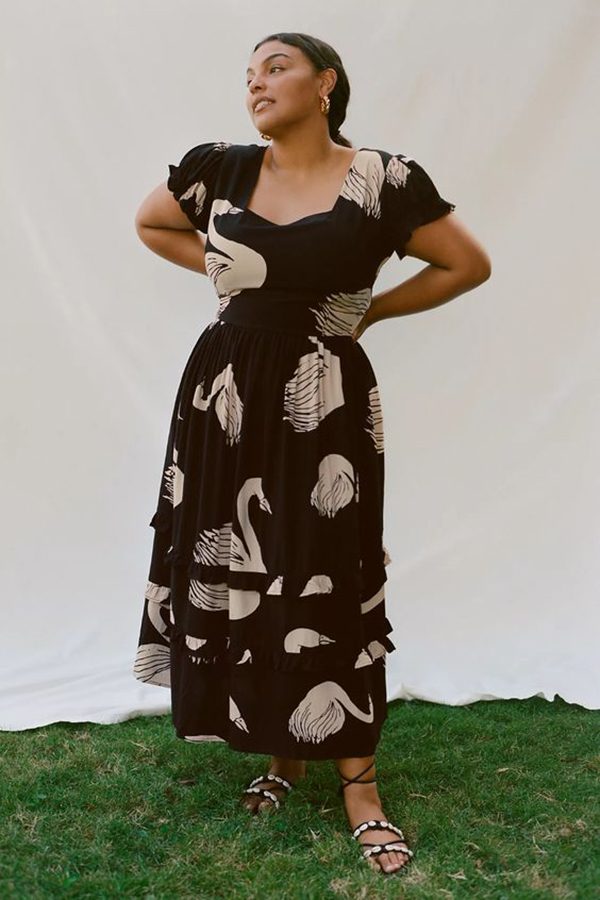 A plus-size model wearing a black printed dress.