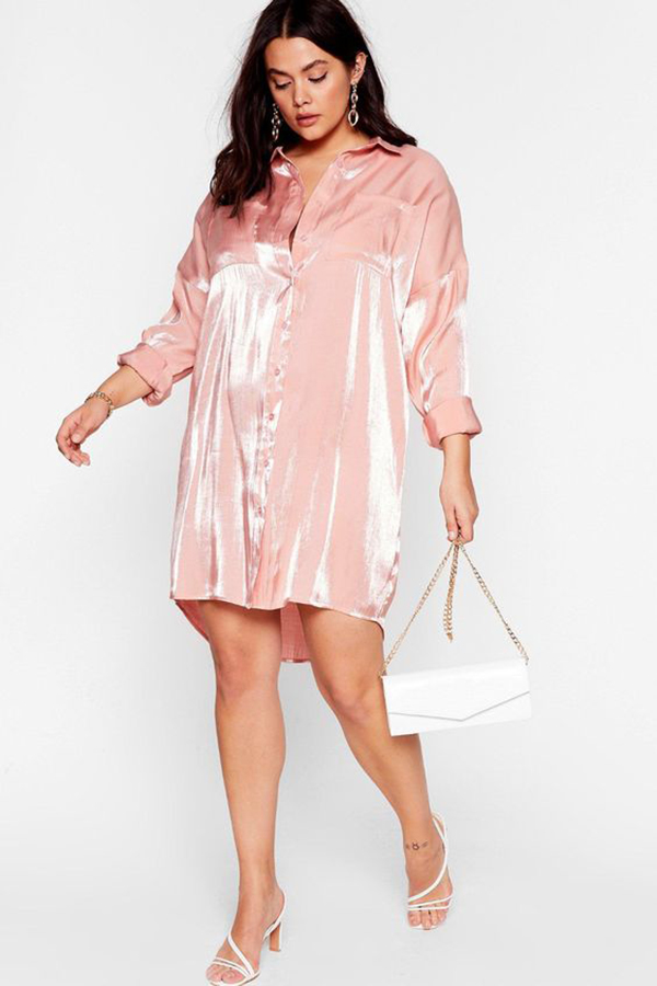 A plus-size model wearing a pink shirt dress.