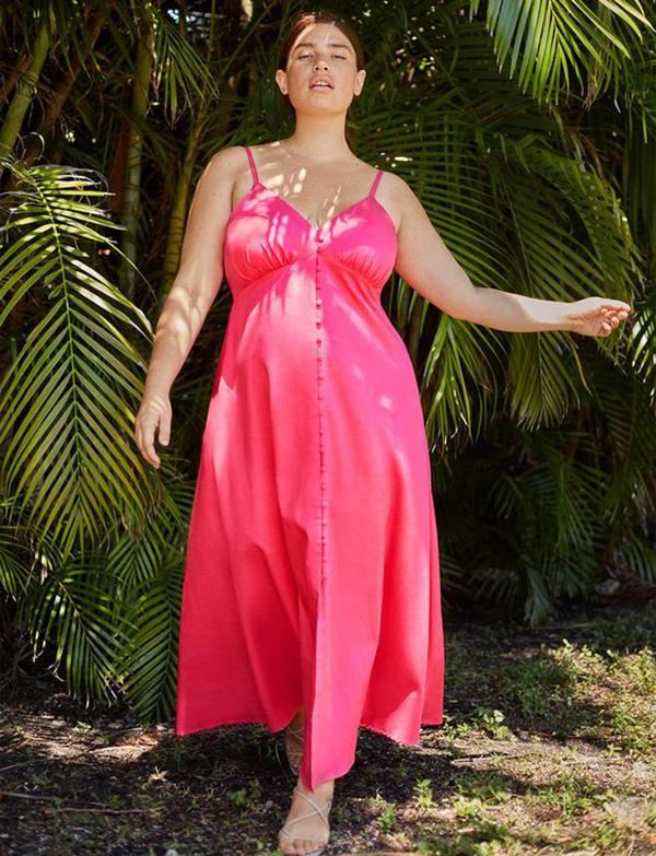 A plus-size model wearing a hot pink maxi dress.