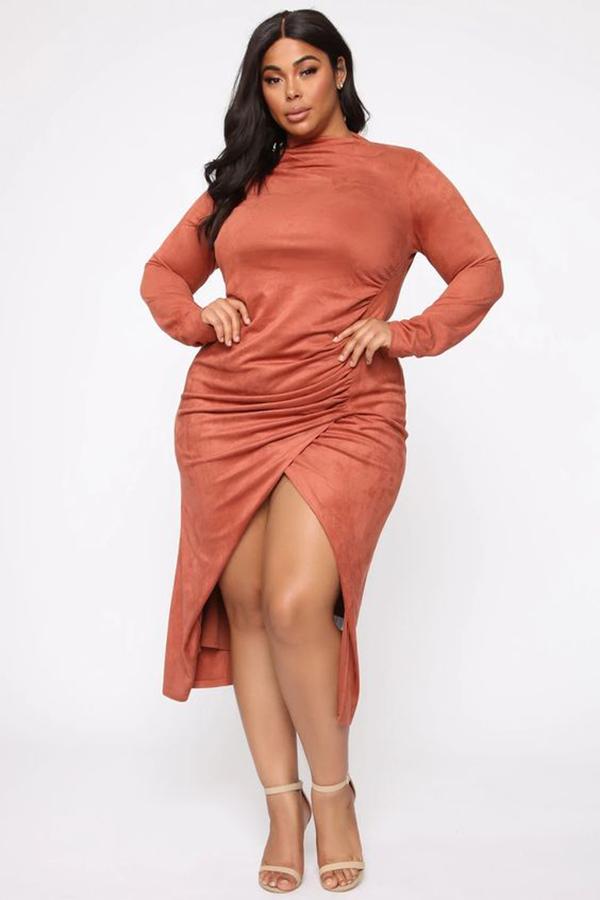 A plus-size model wearing a burnt orange suede dress.