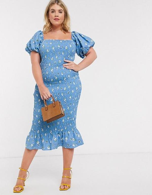A plus-size model wearing a blue floral dress.