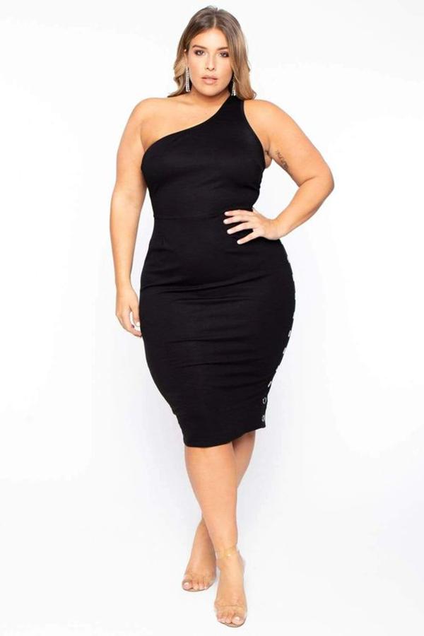 A plus-size model wearing a black one-shoulder dress.