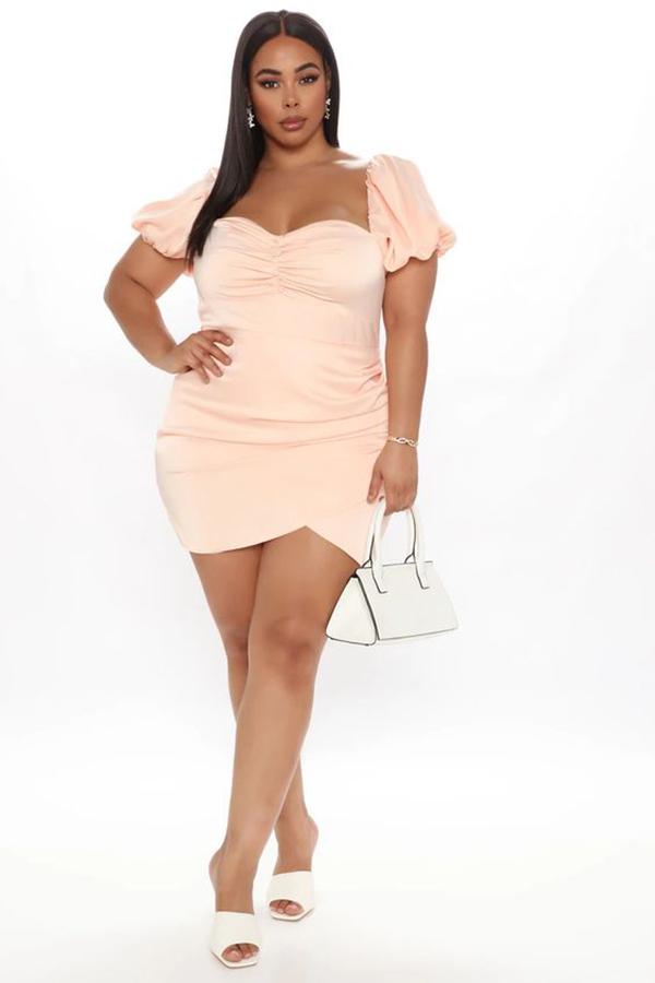 A plus-size model wearing a pink mini dress.