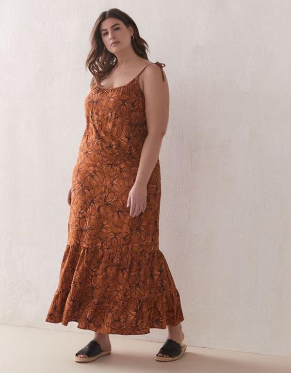 A plus-size model wearing a printed maxi dress.