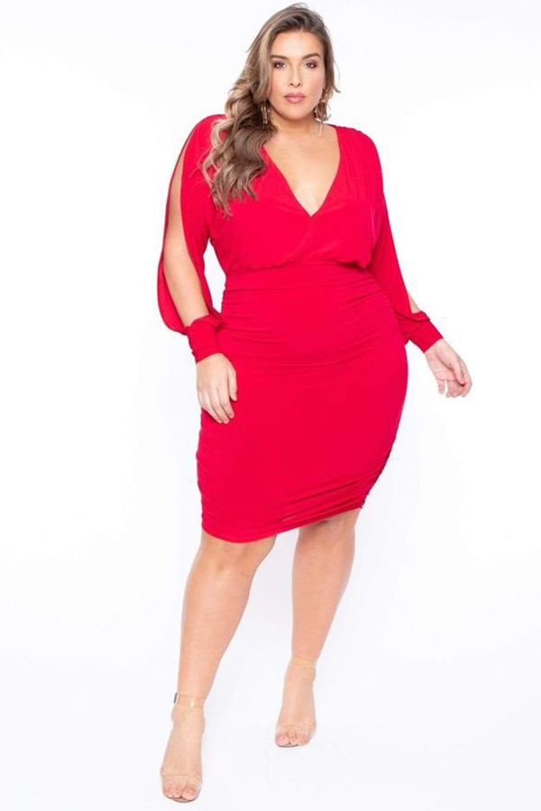A plus-size model wearing a red form-fitting dress.