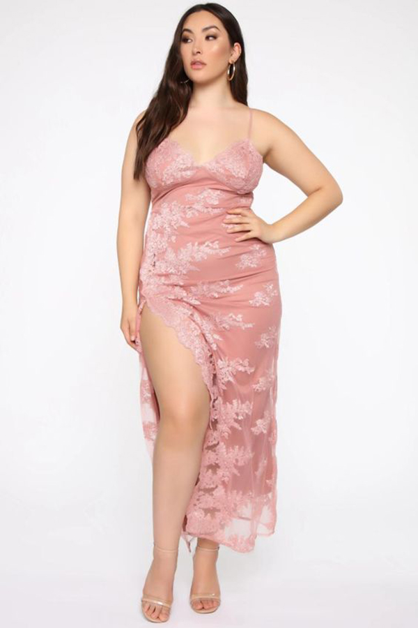 A plus-size model wearing a pink, lace-covered maxi dress.