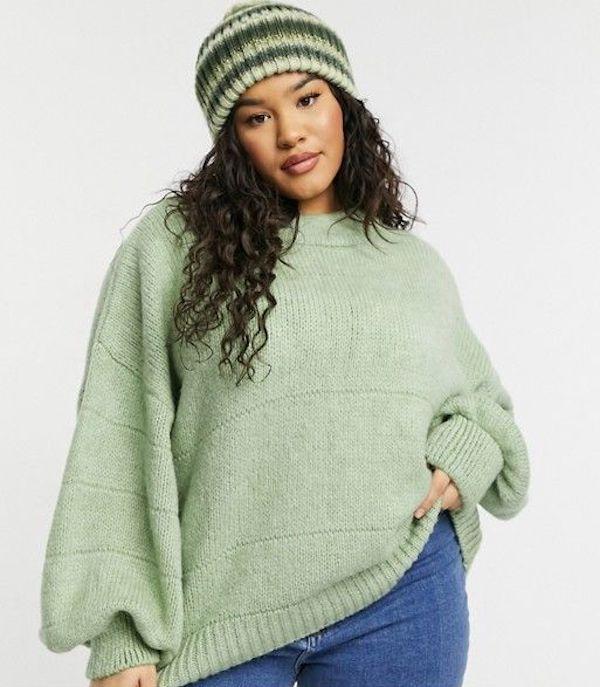 A model wearing a plus-size oversized sweater in light green.