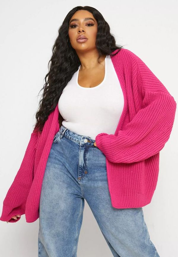 A model wearing a plus-size oversized sweater in hot pink.