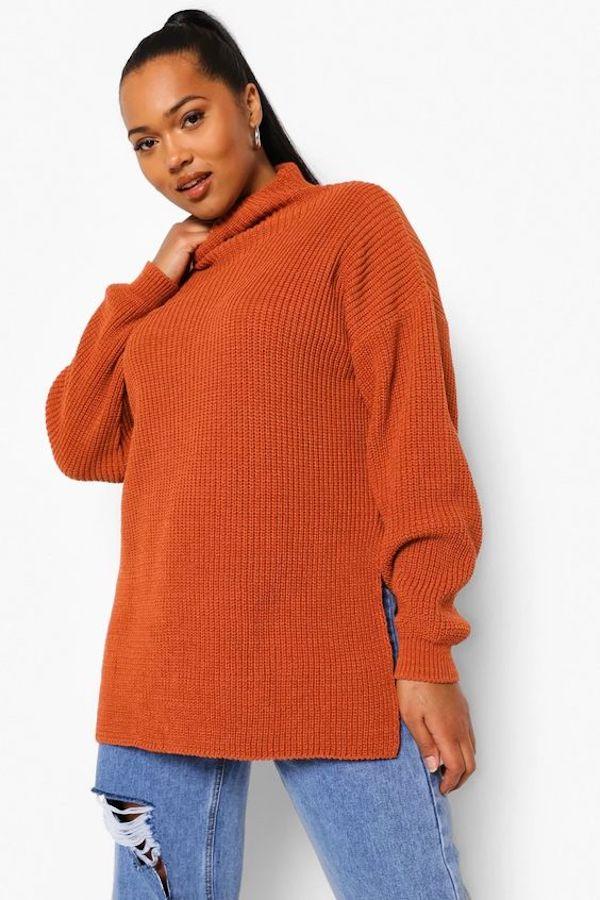 A model wearing a plus-size oversized sweater in burnt orange.