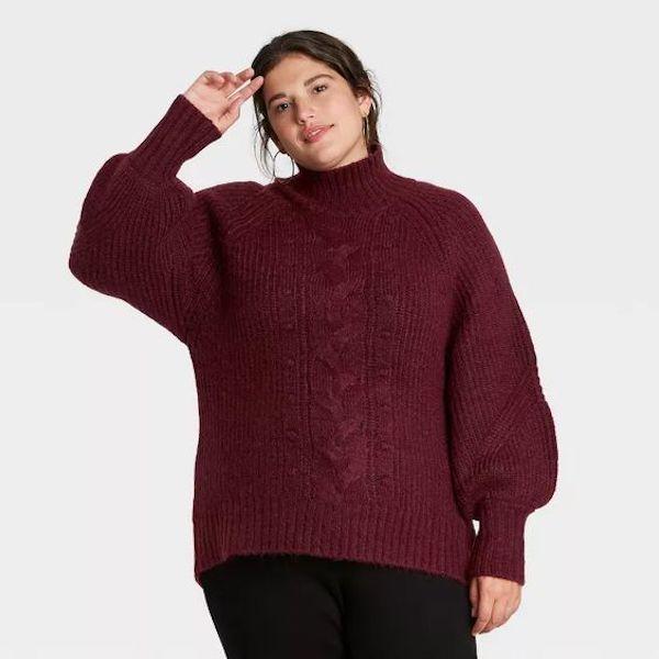 A model wearing a plus-size oversized sweater in dark maroon.