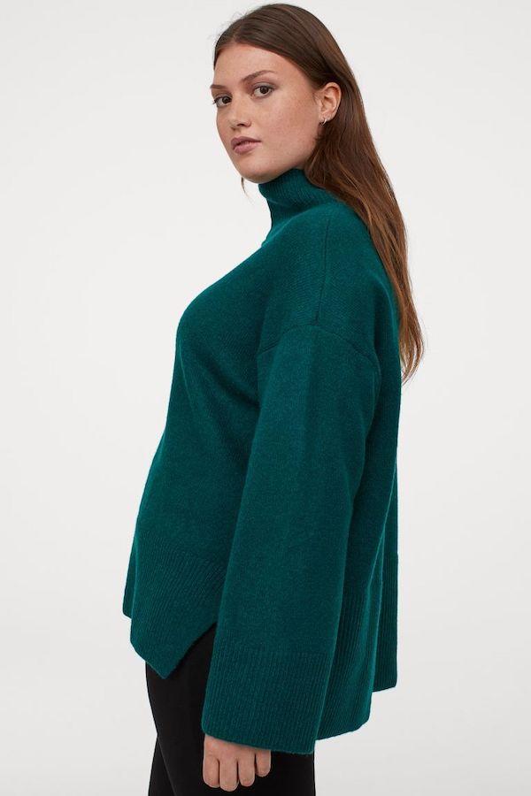 A model wearing a plus-size oversized sweater in emerald green.