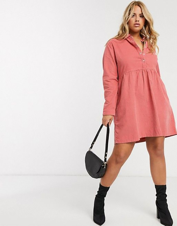 A plus-size model wearing a pink corduroy dress.