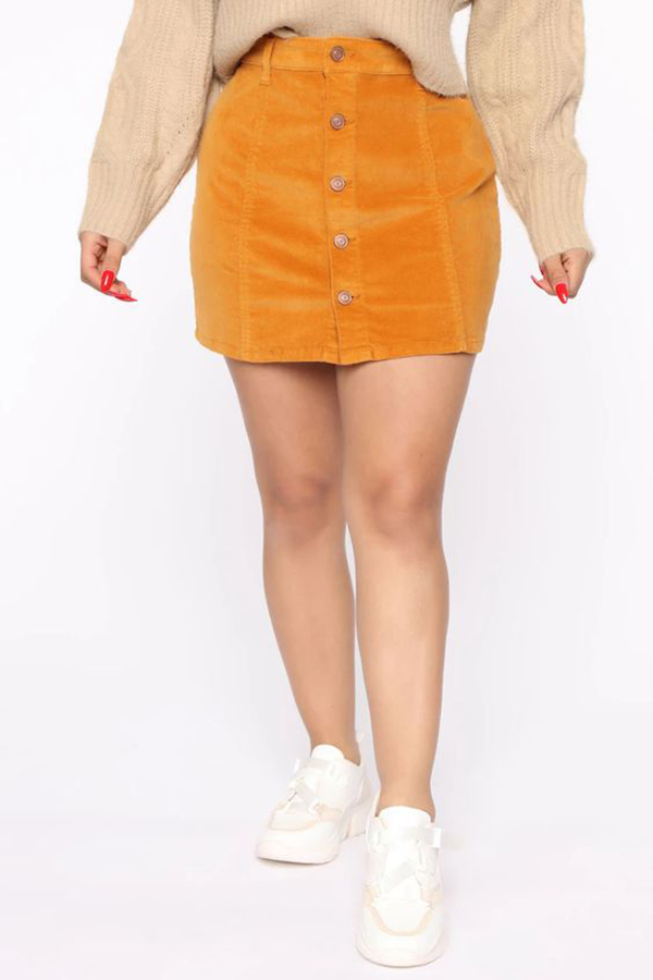 A plus-size model wearing a corduroy skirt.